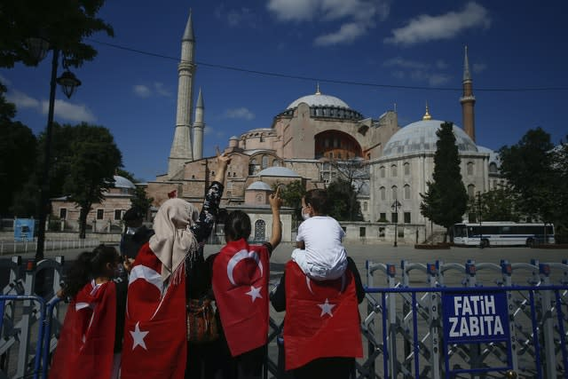 People, draped in Turkish flags stand outside the now closed Byzantine-era Hagia Sophia (Emrah Gurel/AP)