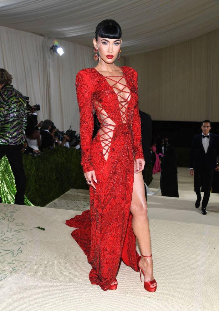 Megan Fox attends The 2021 in a long gown featuring laced up cutouts and rocking a long braided ponytail with blunt bangs