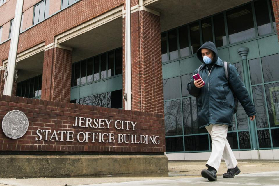 A man wears a face mask as he leaves the Jersey City State Office Building, after it was closed following the outbreak of coronavirus disease (COVID-19), in Jersey City, New Jersey, U.S. March 19, 2020. REUTERS/Eduardo Munoz