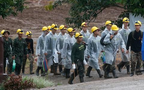 <span>Rescuers walk towards the entrance to the cave on Tuesday morning</span> <span>Credit: Sakchai Lalit /AP </span>