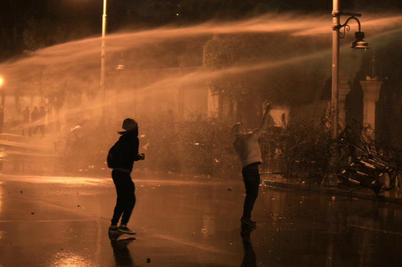 Egyptian protesters throw stones while security police open water canons on them from inside the grounds of the presidential palace during a demonstration in Cairo, Egypt, Monday, Feb. 11, 2013. Security forces sprayed protesters with water hoses and tear gas outside the presidential palace Monday as Egyptians marked the second anniversary of autocrat Hosni Mubarak's ouster with angry demonstrations against his elected successor.(AP Photo/Khalil Hamra)
