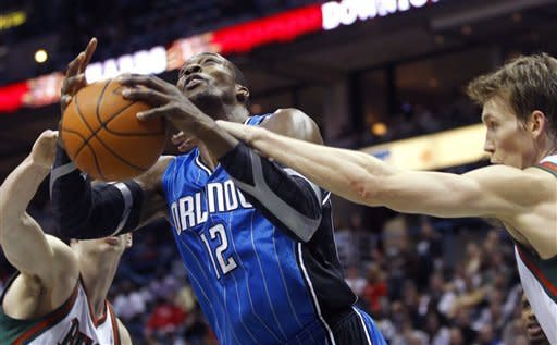 Orlando Magic's Dwight Howard (12) is fouled by Milwaukee Bucks' Mike Dunleavy, right, during the first half of an NBA basketball game, Monday, Feb. 20, 2012, in Milwaukee. (AP Photo/Jeffrey Phelps)
