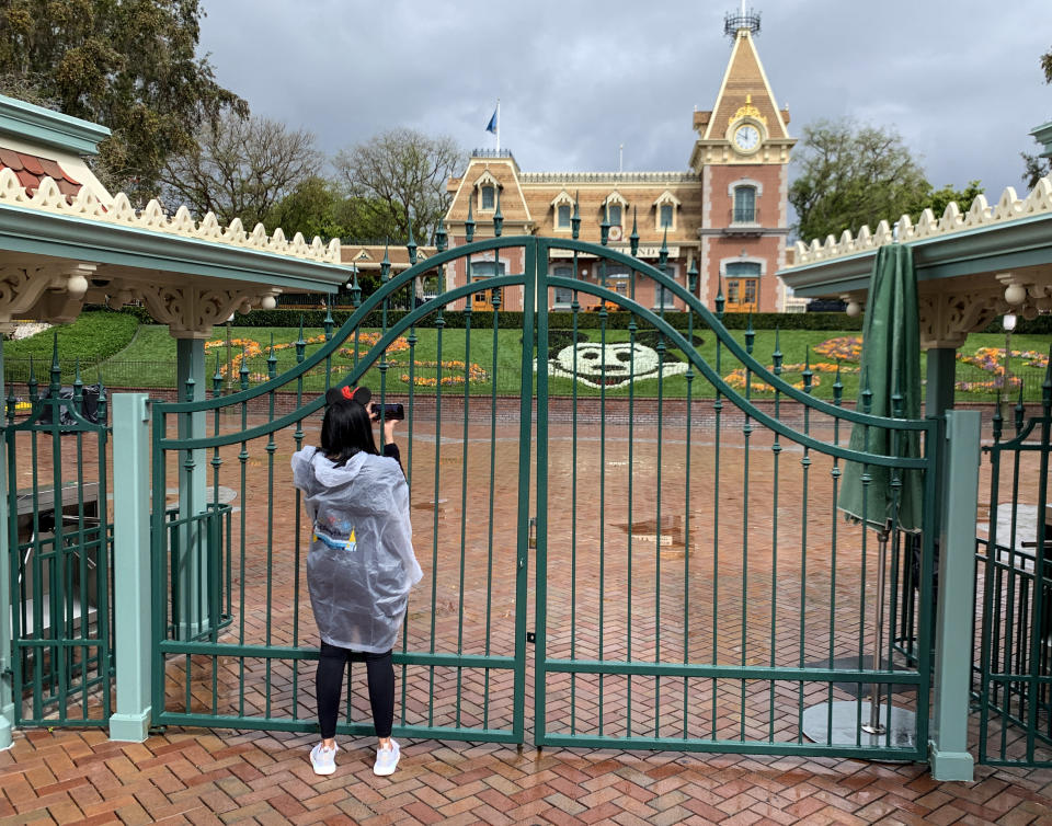 ANAHEIM, CA - MARCH 16: Disney will lay off 28,000 employees at Disneyland and Walt Disney World as the company continues to struggle with the impacts of the COVID-19 pandemic and the six-month closure of its Anaheim theme parks, the company announced today. A visitor to the Disneyland Resort takes a picture through a locked gate at the entrance to Disneyland in Anaheim, CA, on Monday, Mar 16, 2020. The entire Disneyland Resort is shut down due to the coronavirus (COVID-19) outbreak. (Photo by Jeff Gritchen/MediaNews Group/Orange County Register via Getty Images)
