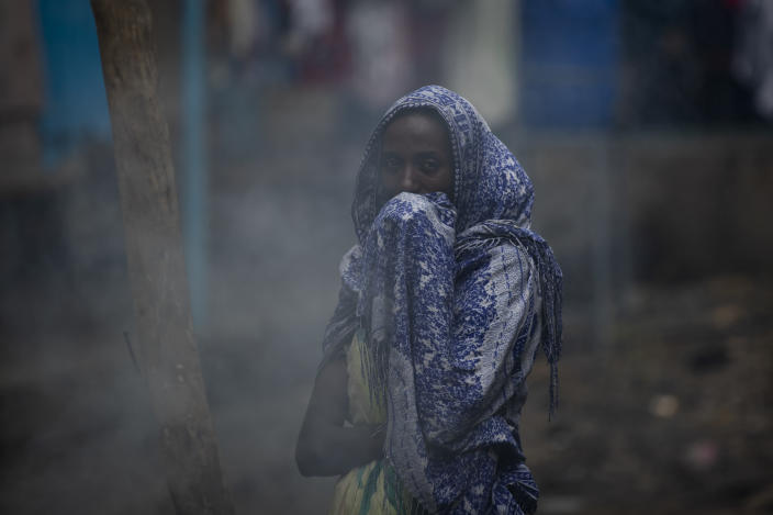 """A displaced Tigrayan woman covers her face from the smoke of a wood fire as she prepares """"Injera"""" flatbread at the Hadnet General Secondary School which has become a makeshift home to thousands displaced by the conflict, in Mekele, in the Tigray region of northern Ethiopia Wednesday, May 5, 2021. The Tigray conflict has displaced more than 1 million people, the International Organization for Migration reported in April, and the numbers continue to rise. (AP Photo/Ben Curtis)"""