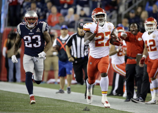 Kansas City Chiefs running back Kareem Hunt (27) runs from New England Patriots safety Patrick Chung (23) during the second half of an NFL football game, Friday, Sept. 8, 2017, in Foxborough, Mass. (AP Photo/Steven Senne)