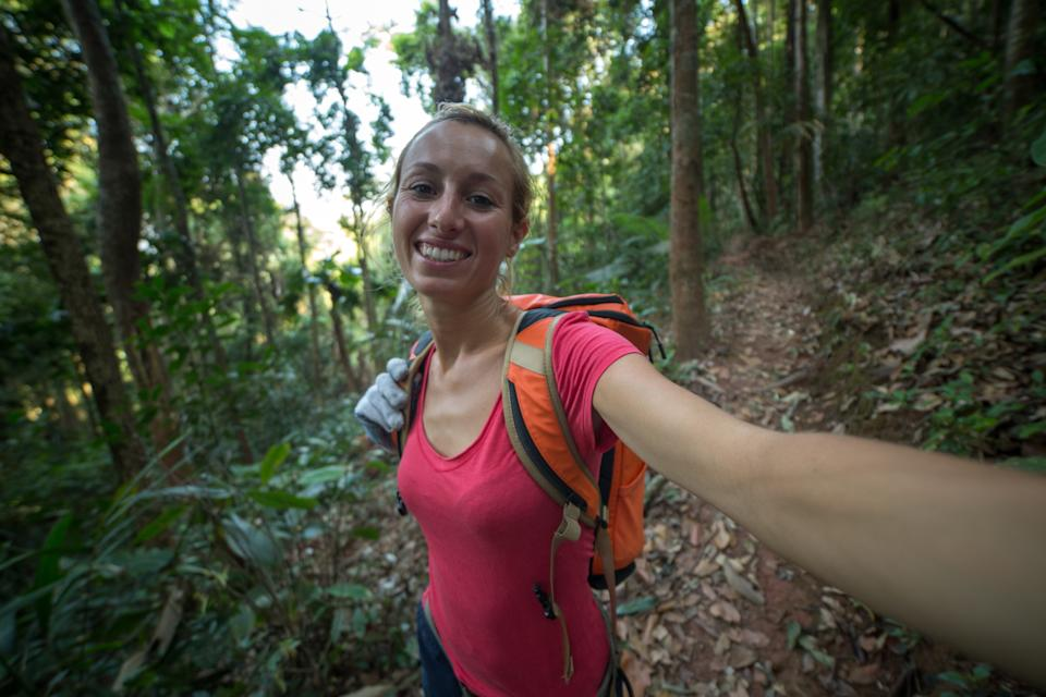 Young healthy woman enjoying hiking on a canopy tour adventure in the rain forest in northern Laos, sunny summer day.