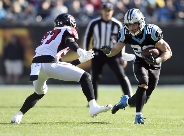 Carolina Panthers' Christian McCaffrey (22) runs as Atlanta Falcons' Damontae Kazee (27) defends during the first half of an NFL football game in Charlotte, N.C., Sunday, Dec. 23, 2018. (AP Photo/Mike McCarn)
