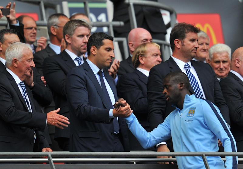 Manchester City's Yaya Toure (front R) shakes hands with Man City's chairman Khaldoon al-Mubarak as he receives his runners-up medal after loosing their FA Community Shield match against Arsenal, at Wembley Stadium in London, on August 10, 2014 (AFP Photo/Glyn Kirk)