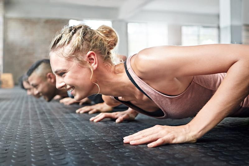 Shot of a group of people doing push ups in a gym