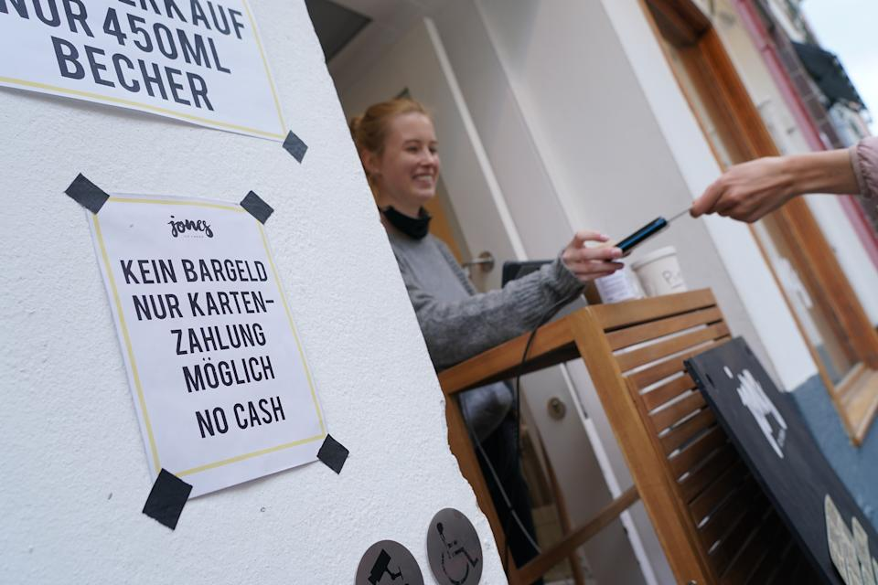 BERLIN, GERMANY - APRIL 29: A sign notifies customers of no cash payments as a customer pays with a credit card at Jones ice cream shop in Schoeneberg district during the novel coronavirus crisis on April 29, 2020 in Berlin, Germany. Many retailers are switching to non-cash payment options as a means to protect staff from infection with the virus. (Photo by Sean Gallup/Getty Images)