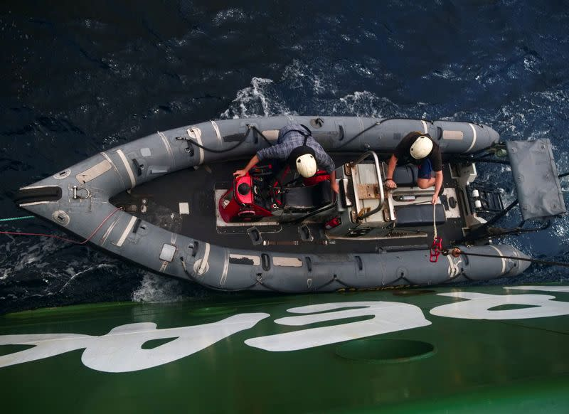 Arctic Sunrise ship crew members are seen on a rigid inflatable boat as it is lowered into the Indian Ocean at the Saya de Malha Bank