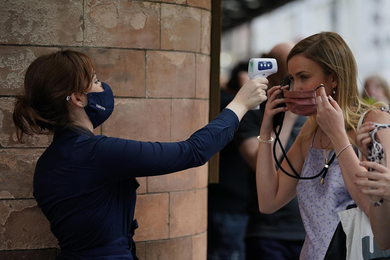 A woman has her temperature checked in the queue for The Show Must Go On Live at the Palace Theatre in London. Picture date: Wednesday June 2, 2021.
