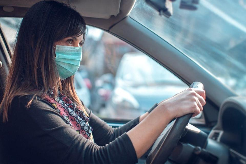 woman driving car with face mask