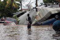 FILE - In this Nov. 6, 2020 file photo, a resident walking through a flooded street looks back at storm damage caused by Hurricane Eta in Planeta, Honduras. Flooded out Honduran and Guatemalan families stranded on rooftops in the most marginalized neighborhoods after the passage of hurricanes Eta and Iota portend a new wave of migration, observers across the region say. (AP Photo/Delmer Martinez, File)