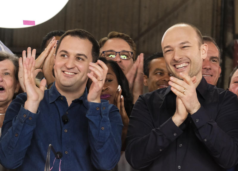 """Lyft co-founders John Zimmer, left, and Logan Green cheer as they as they ring a ceremonial opening bell in Los Angeles, Friday, March 29, 2019. On Friday the San Francisco company's stock will begin trading on the Nasdaq exchange under the ticker symbol """"LYFT."""" (AP Photo/Ringo H.W. Chiu)"""