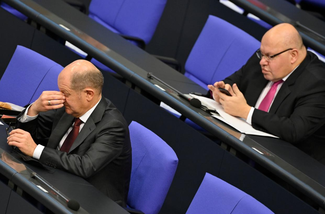 German Finance Minister and Vice-Chancellor Olaf Scholz (L) gestures as German Economy Minister Peter Altmaier checks his mobile phone during a debate at the Bundestag (lower house of parliament) in Berlin on December 8, 2020. (Photo by John MACDOUGALL / AFP) (Photo by JOHN MACDOUGALL/AFP via Getty Images)
