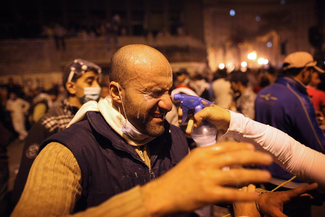 CAIRO, EGYPT - NOVEMBER 22:  A prototestor receives a spray to help counteract the effects of tear gas near Tahrir Square on November 22, 2011 in Cairo, Egypt. Thousands of Egyptians have been gathering in Tahrir Square after three days of deadly clashes with security forces despite a promise from Egypt's interim ruling Military council to bring forward Presidential elections. (Photo by Peter Macdiarmid/Getty Images)