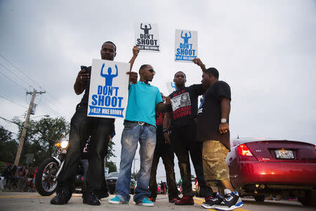Demonstrators gesture and chant as they continue to react to the shooting of Michael Brown in Ferguson, Missouri