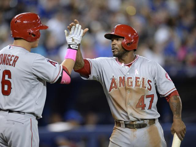 Los Angeles Angels' Howie Kendrick, right, celebrates with teammate Hank Conger after scoring against the Toronto Blue Jays during fourth-inning baseball game action in Toronto, Sunday, May 11, 2014. (AP Photo/The Canadian Press, Frank Gunn)