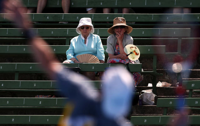 Two ladies with fans watch France's Paul-Henri Mathieu serve during his match against Italy's Simone Bolelli at the Kooyong Classic tennis tournament in Melbourne January 10, 2013. REUTERS/David Gray (AUSTRALIA - Tags: SPORT TENNIS TPX IMAGES OF THE DAY)