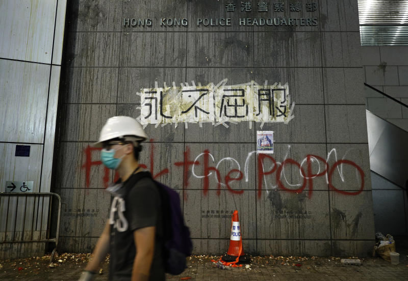 """A protester walks past a wall outside the police headquarters with eggs thrown by protestors and a banner reading """"Never Give In"""" in Hong Kong, Friday, June 21, 2019. More than 1,000 protesters blocked Hong Kong police headquarters into the evening Friday, while others took over major streets as the tumult over the city's future showed no signs of abating. (AP Photo/Vincent Yu)"""
