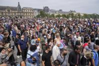 Anti-vaccine protesters march during a rally in Paris, Saturday, July 17, 2021. Tens of thousands of people protested across France on Saturday against the government's latest measures to curb rising COVID-19 infections and drive up vaccinations in the country. The Louvre museum in the background. (AP Photo/Michel Euler)