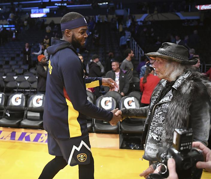 James Goldstein shakes hands with Denver Nuggets forward Paul Millsap in 2019