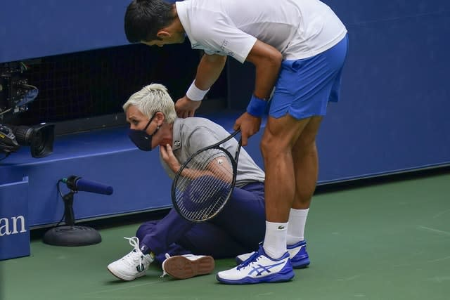 Djokovic checks on the condition of the line judge as she holds her throat