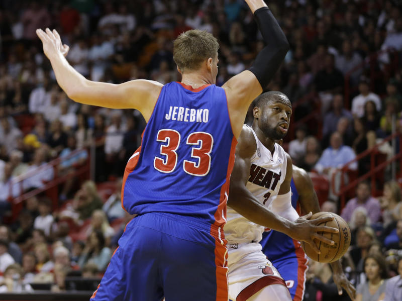 Detroit Pistons' Jonas Jerebko (33) forces Miami Heat's Dwyane Wade (3) to pass the ball off during the first half of a NBA basketball game in Miami, Friday, March 22, 2013. (AP Photo/J Pat Carter)
