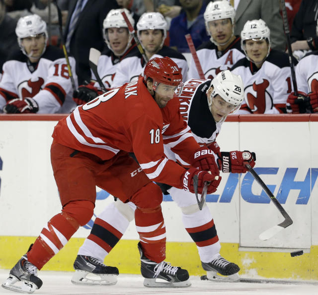 Carolina Hurricanes' Radek Dvorak (18), of the Czech Republic, and New Jersey Devils' Anton Volchenkov (28), of Russia, chase the puck during the first period of an NHL hockey game in Raleigh, N.C., Saturday, April 5, 2014. (AP Photo/Gerry Broome)