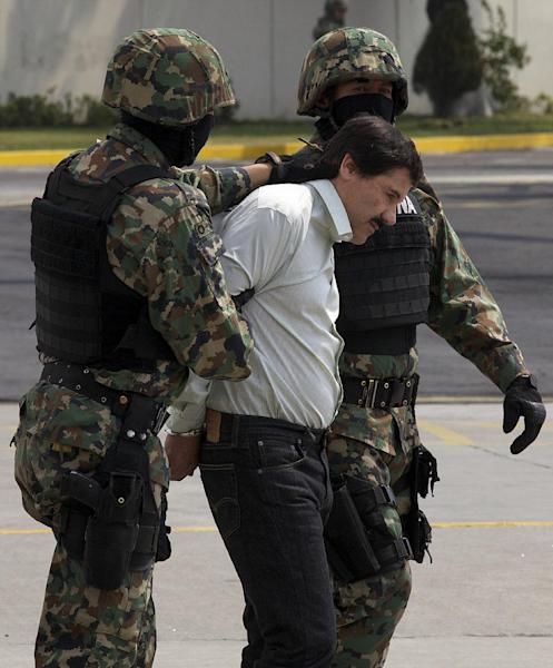 "Joaquin ""El Chapo"" Guzman is escorted to a helicopter in handcuffs by Mexican navy marines at a navy hanger in Mexico City, Mexico, Saturday, Feb. 22, 2014. After 13 years on the run, narrow escapes from the military, law enforcement and rivals, Guzman is back in Mexican custody. Now starts what is likely to be a lengthy and complicated legal process to decide which country gets to try him first. (AP Photo/Dario Lopez-Mills)"