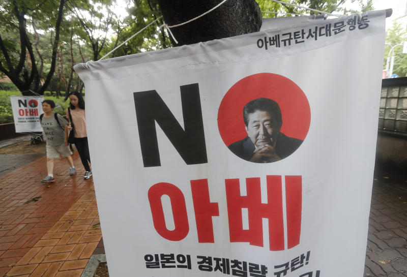 "People pass by a banner with an image of Japanese Prime Minister Shinzo Abe to denounce Japan's trade restrictions on South Korea on a street in Seoul, South Korea, Monday, Aug 12, 2019. South Korea said Monday that it has decided to remove Japan from a list of nations receiving preferential treatment in trade in what was seen as a countermeasure to Tokyo's recent decision to downgrade Seoul's trade status amid a diplomatic row. The sign reads ""No Abe."" (AP Photo/Ahn Young-joon)"