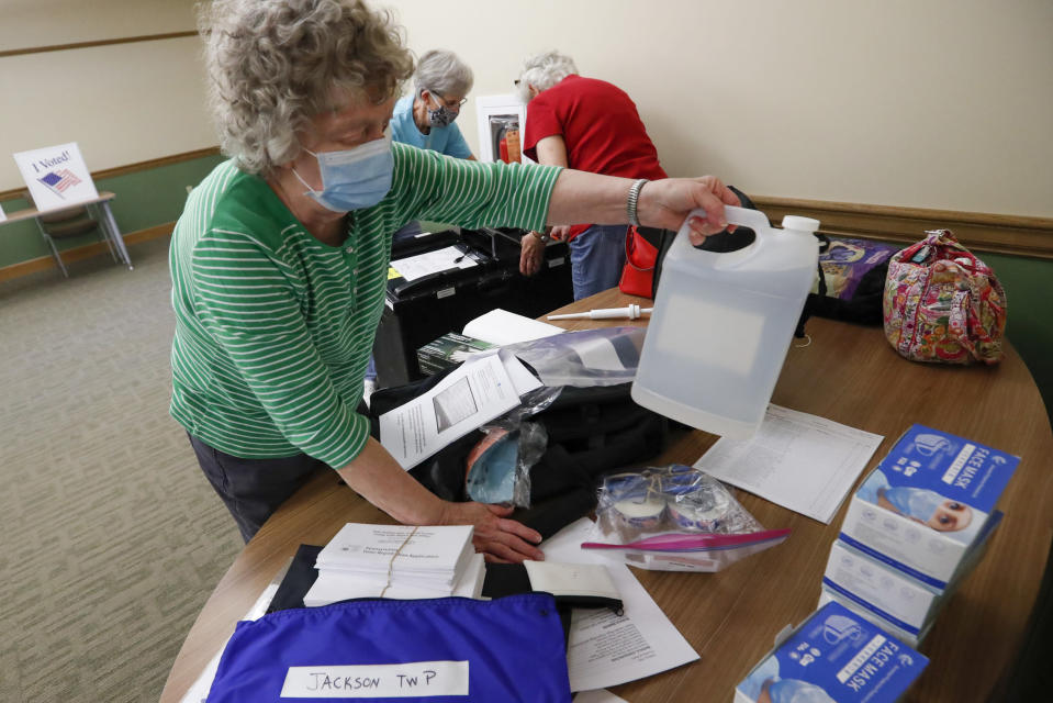 Marty Goetz, left, unpacks a bottle of alcohol from the COVID-19 prep kit as they start to set up their polling place Monday, June 1, 2020, for the voting for Tuesday's Pennsylvania primary in Jackson Township near Zelienople, Pa. (AP Photo/Keith Srakocic)