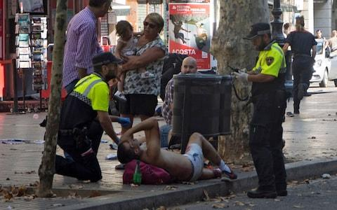 Police speak to an injured person at the scene. Local media report the van driver ran away
