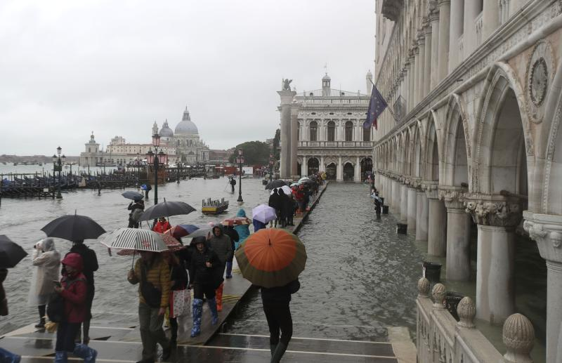 People walk on catwalk set up on the occasion of a high tide, in a flooded Venice, Italy, Tuesday, Nov. 12, 2019. (Photo: Luca Bruno/AP)