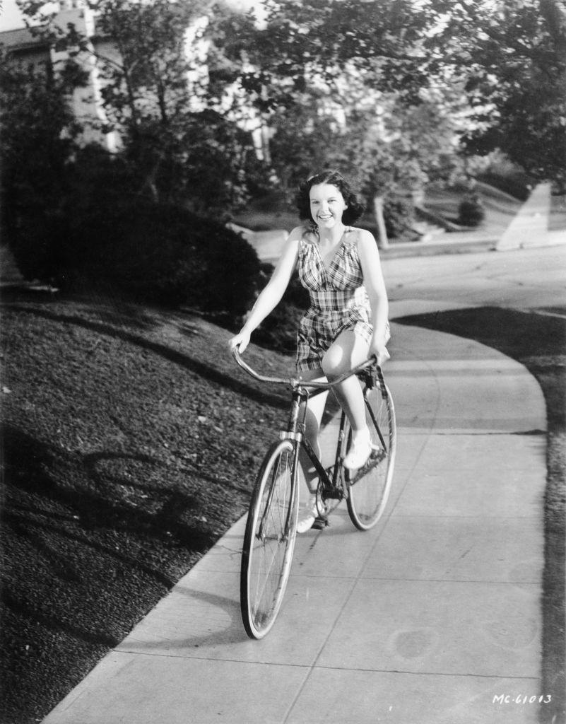 <p>Garland bikes down a street dressed in a charming checked romper and sporting a soft curl in her hair, a true American, girl-next-door look for this time that she wore so well. </p>