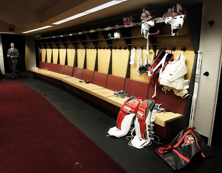 FILE - This Sept. 16, 2004 file photo shows an Ottawa Senators employee walking into the player's empty dressing room with goaltender Dominik Hasek's equipment sitting on the bench, in Ottawa, on the first day of a lockout. With a lockout drawing ever closer, the NHL and the players' union are in touch with each other after a day of internal meetings. But no new negotiating sessions are scheduled for Friday, Sept. 14, 2012, one day before Commissioner Gary Bettman has said he will lock out the players. This would be the NHL's fourth work stoppage since 1992. (AP Photo/Tom Hanson, FIle)