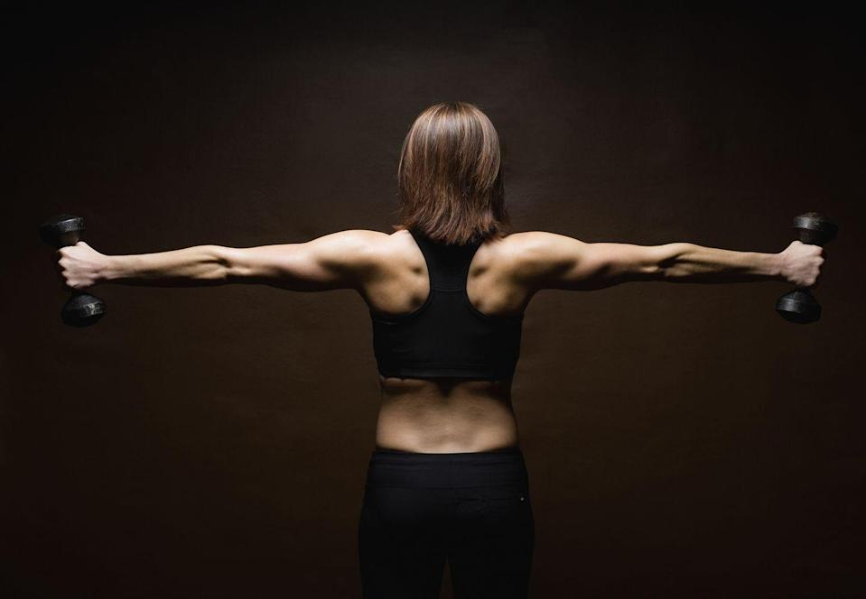 """<p>""""Building scapular control and stability removes the traps from the equation and helps us to engage muscles we never even knew we had. This exercise does not require a lot of weight but will do wonders to build up strength in your rotator cuff as well as your back,"""" says McKinney. </p><p><strong>How to: </strong>Stand tall with feet hip-width apart and hold a very light dumbbell in each hand. Engage your core, and pull your shoulders back and down. Push your hips back until your chest is at a 45-degree angle from your hips, and maintain this fixed position for the entirety of the movement. Your arms should be fully extended and hanging underneath you with your weights in hand, and you'll draw these three different letters using your arms. Complete rounds of 5-6 reps through each letter.</p><p>For I's, pull your arms up until they are framing your face in an overhead position then lower them back down. </p><p>For Y's, pull your arms out at a 45-degree angle until your shoulder has full opened, then lower your arms back down. </p><p>For T's, same idea here but pull your arms out completely wide to make a T with your body. </p>"""