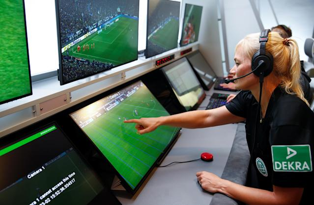 """Bibiana """"Bibi"""" Steinhaus, 40, Germany's first female referee in its first soccer division Bundesliga, points at reference lines on a screen to call an offside during a media workshop at the German Football League (DFL) video assistant referee (VAR) centre in Cologne, Germany, August 5, 2019. REUTERS/Wolfgang Rattay"""