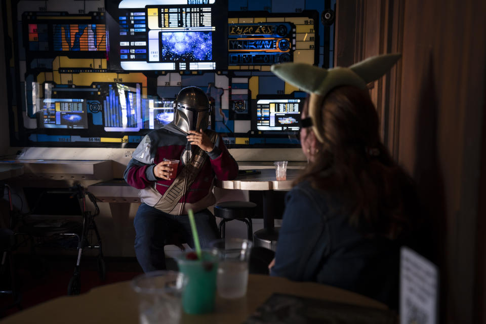 Two fans chat while celebrating the Star Wars Day at Scum and Villainy Cantina, a bar located on Hollywood Blvd, in Los Angeles, Tuesday, May 4, 2021. California has the lowest infection rate in the country. Los Angeles County, which is home to a quarter of the state's nearly 40 million people and has endured a disproportionate number of the state's 60,000 deaths, didn't record a single COVID-19 death Sunday or Monday, which was likely due to incomplete weekend reporting but still noteworthy. (AP Photo/Jae C. Hong)