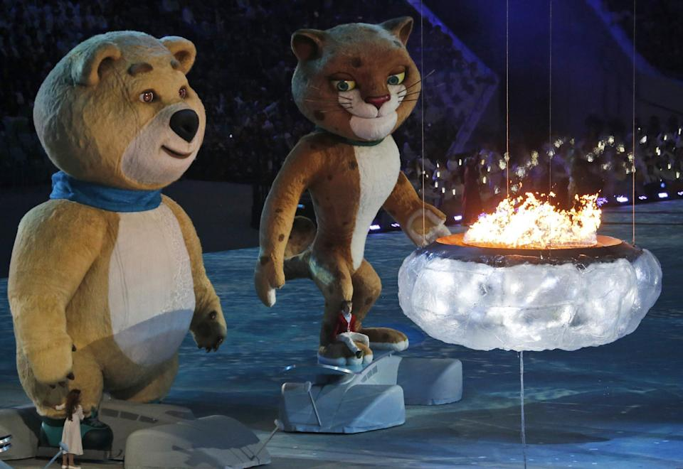 A polar bear and a leopard, mascots of Sochi 2014, approach a flame representing the burning Olympic cauldron, during the closing ceremony of the 2014 Winter Olympics, Sunday, Feb. 23, 2014, in Sochi, Russia. (AP Photo/Dmitry Lovetsky)