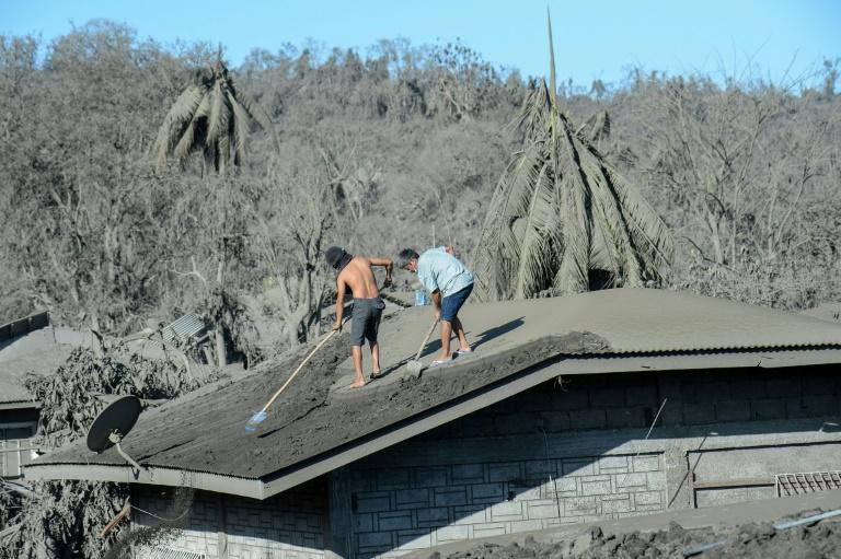 Residents clean the roof of their home covered in mud and ash due to the eruption of the nearby Taal volcano at a village in Laurel, Batangas province (AFP Photo/Ted ALJIBE)