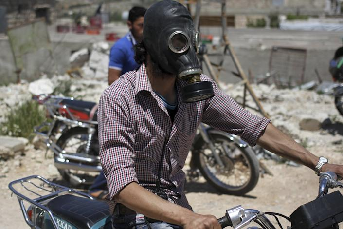 A man drives his motorcycle as he wears a gas masks after what activists said was a chlorine gas attack on Kansafra village at Idlib countryside, Syria May 7, 2015. REUTERS/Abed Kontar