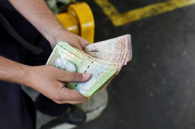 A worker counts Venezuelan bolivar notes at a gas station of Venezuelan state oil company PDVSA in Caracas