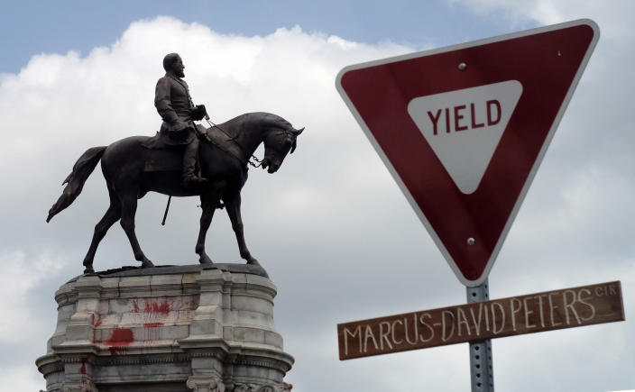 The graffiti-smeared statue of Robert E. Lee and Traveller stand behind a traffic sign with Marcus-David Peters Circle on a handwritten sign below on the circle that surrounds the monument on Monument Avenue in Richmond, Va., Wednesday, June 10, 2020. Peters was the man suffering a mental condition who was shot by a Richmond police officer several years ago. Police arrested a man and seized three assault-style rifles and one handgun after a late-night confrontation near the city's statue of Confederate General Robert E. Lee, authorities said Friday, June 12, 2020. (Bob Brown/Richmond Times-Dispatch via AP)