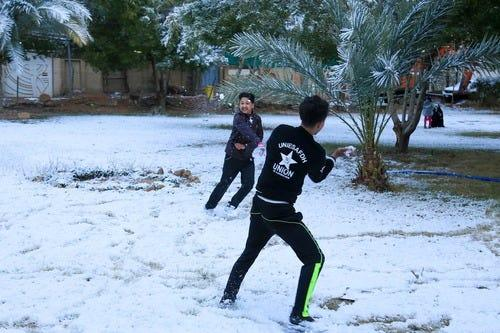 Iraqi boys play in the snow in the city of Karbala on Feb. 11. Iraq's capital, Baghdad, woke up covered in a thin layer of snow, an extremely rare phenomenon for one of the world's hottest countries.