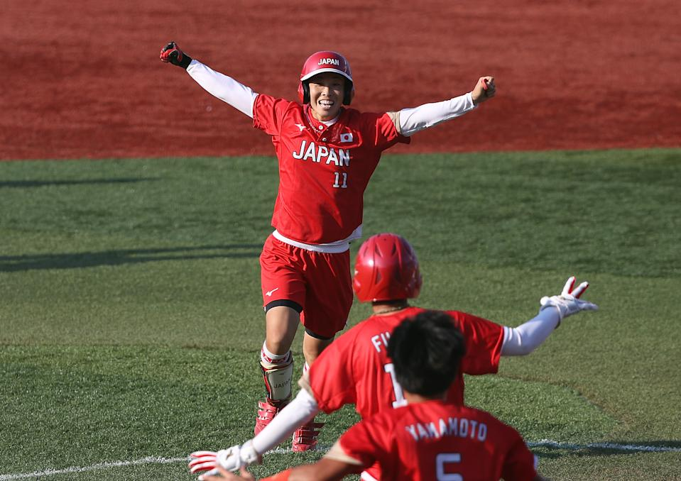 <p>YOKOHAMA, JAPAN - JULY 25: Eri Yamada #11 of Team Japan celebrates her game-winning RBI in the eighth inning against Team Canada with teammates during the Softball Opening Round on day two of the Tokyo 2020 Olympic Games at Yokohama Baseball Stadium on July 25, 2021 in Yokohama, Kanagawa, Japan. Team Japan defeated Team Canada 1-0. (Photo by Yuichi Masuda/Getty Images)</p>
