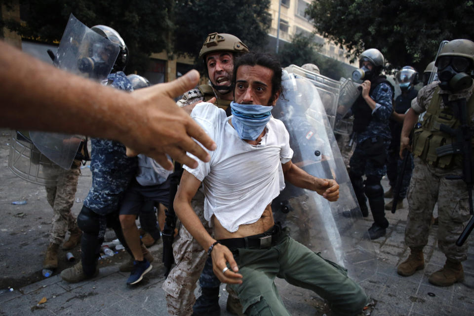 A protestor is evacuated from clashes during a protest against the political elites and the government after this week's deadly explosion at Beirut port which devastated large parts of the capital in Beirut, Lebanon, Saturday, Aug. 8, 2020. (AP Photo/Thibault Camus)