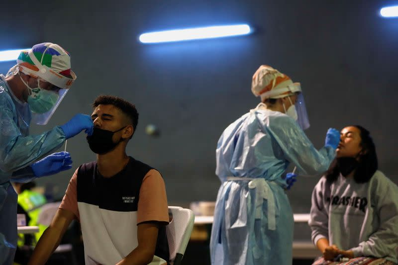 Health workers take swabs during a voluntary antigen test for the coronavirus disease (COVID-19) of young people coming back from vacationing in Salou at the bus station in Pamplona