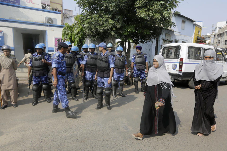 Indian women walk past Rapid Action Force (RAF) personnel standing guard in Ahmadabad, India, Saturday, Nov. 9, 2019. India's Supreme Court has ruled in favor of a Hindu temple on a disputed religious ground and ordered that alternative land be given to Muslims. The dispute over land ownership has been one of the country's most contentious issues. (AP Photo/Ajit Solanki)